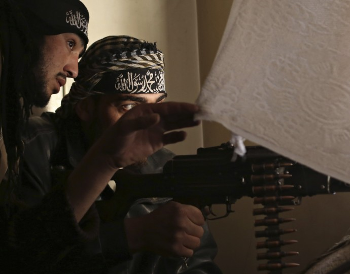 Fighters from the Free Syrian Army's Tahrir al Sham brigade look out of a window before they fire at Syrian Army during a heavy fighting in Mleha suburb of Damascus January 25, 2013. (Goran Tomasevic/Reuters)