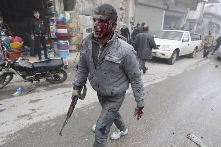 A Free Syrian Army Fighter, covered with blood, walks along a street after what activists said was a missile attack by a Syrian Air Force fighter jet from forces loyal to Syria's President Bashar al-Assad, at the souk of Azaz, north of Aleppo, January 13, 2013. (Muzaffar Salman/Reuters)