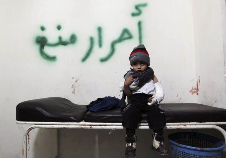 """A wounded child sits on a stretcher as he is treated in a temporary medical center after he was injured during a shelling by forces loyal to President Bashar al Assad, in Aleppo January 10, 2013. The graffiti behind reads: """"Liberate Meng (area)"""". (Muzaffar Salman/Reuters)"""