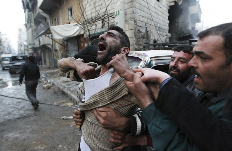 A father reacts after the death of two of his children, whom activists said were killed by shelling by forces loyal to Syria's President Bashar al-Assad, at al-Ansari area in Aleppo. (Muzaffar Salman/Reuters)
