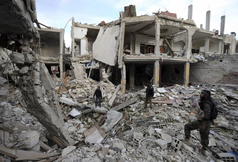 Free Syrian Army fighters walk in the rubble of buildings destroyed by Syrian Army air strikes in the Arabeen neighborhood of Damascus January 24, 2013. (Goran Tomasevic/Reuters)