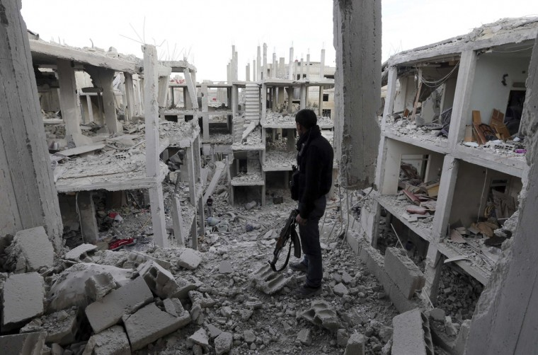 A Free Syrian Army fighter stands in front of the building destroyed by Syrian Army air strikes in the Arabeen neighborhood of Damascus January 24, 2013. (Goran Tomasevic/Reuters)