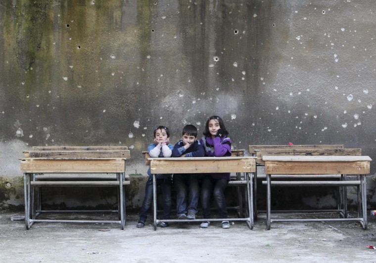 Children sit on school benches at Al-Tawheed school in Aleppo January 1, 2013. (Muzaffar Salman/Reuters)