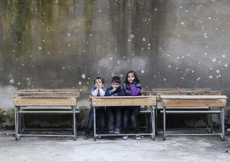 Children sit on school benches at Al-Tawheed school in Aleppo January 1, 2013. (Muzaffar Salman/Reuters)