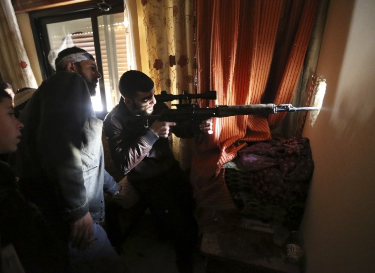 A Free Syrian Army fighter fires a sniper rifle at Syrian Army check point in Haresta neighborhood of Damascus. (Goran Tomasevic/Reuters)
