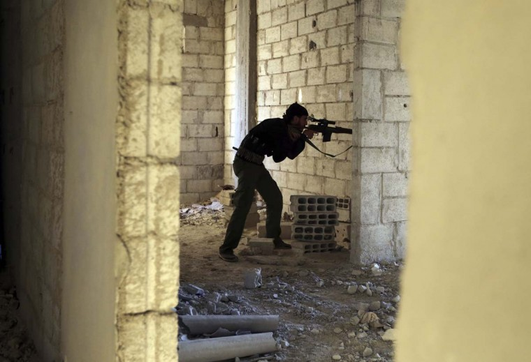 A Free Syrian Army fighter member of Sadik unit aims his Draganov sniper rifle at Syrian Army soldiers in Ain Tarma neighbourhood of Damascus January 20, 2013. (Goran Tomasevic/Reuters)
