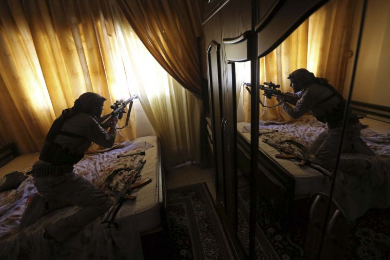 A Free Syrian Army fighter member of Sadik unit of Tahrir al Sham brigade fires his Draganov sniper rifle from inside a house during heavy fighting in Mleha suburb of Damascus January 22, 2013. (Goran Tomasevic/Reuters)