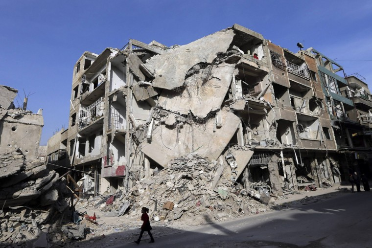 A girl walks past buildings destroyed by Syrian air force air strikes in Duma neighborhood, Damascus. (Goran Tomasevic/Reuters)