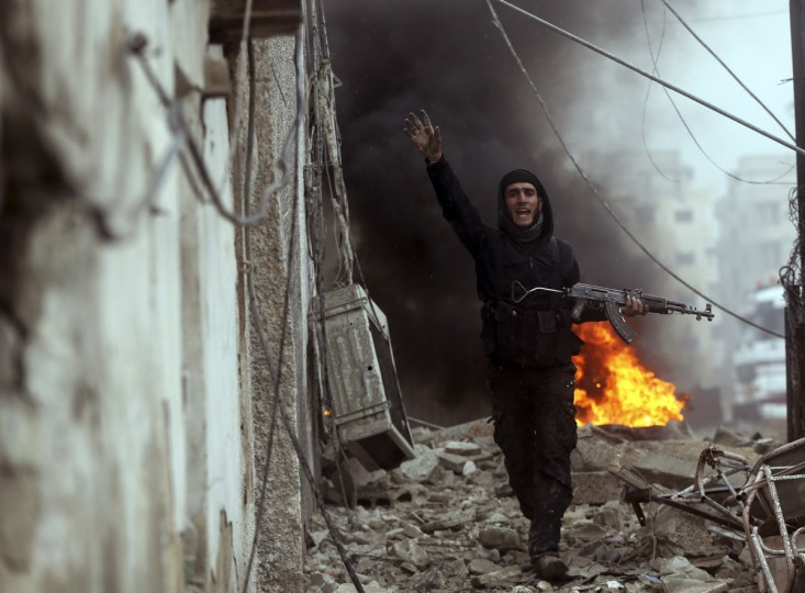 A Free Syrian Army fighter gestures in front of a burning barricade during heavy fighting in the Ain Tarma neighborhood of Damascus January 30, 2013. (Goran Tomasevic/Reuters)