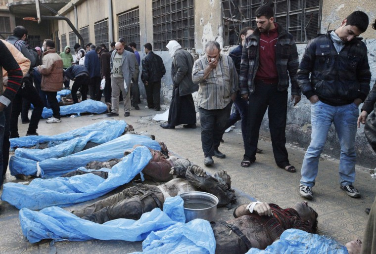 Residents attempt to identify bodies found along a river at a school used as a field hospital in Aleppo's Bustan al-Qasr January 29, 2013. At least 65 people, apparently shot in the head, were found dead with their hands bound in a district of the northern Syrian city of Aleppo on Tuesday, activists said. Opposition activists posted a video of a man filming at least 51 muddied male bodies alongside what they said was the Queiq River in the rebel-held Bustan al-Qasr neighborhood of Aleppo. (Zain Karam/Reuters)