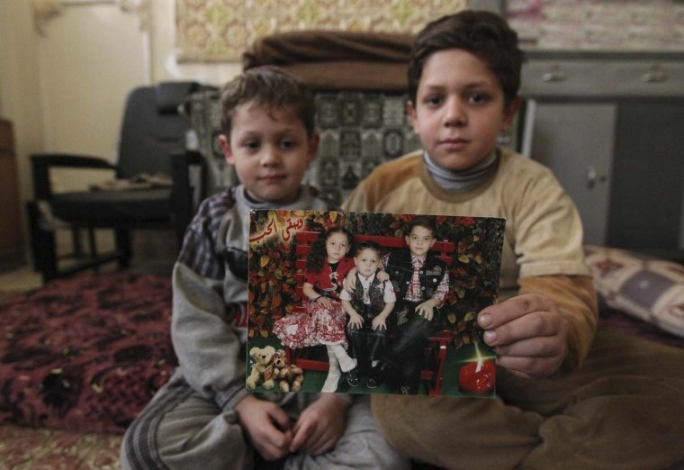 Internally displaced Syrian boys, Mohamed and Khalil (R), show a picture they took with their sister, whom they said died during a bombing at the school where they were staying, in Aleppo January 14, 2013. (Muzaffar Salma/Reuters)