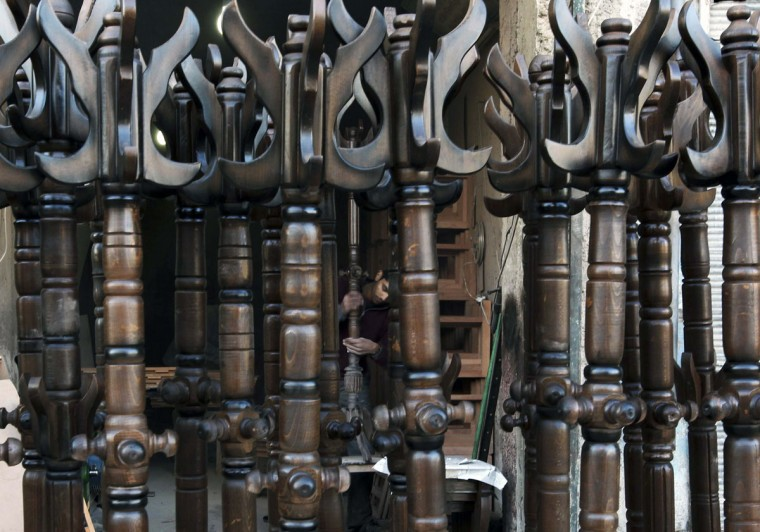 A man works at a shop selling wood coat-stands in Aleppo, Syria. (Muzaffar Salman /Reuters)