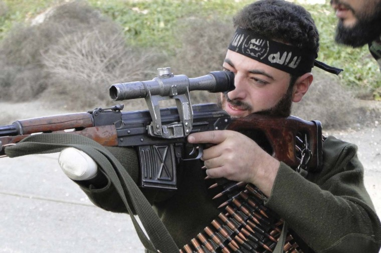 A Free Syrian Army fighter, with an amputated hand, points his weapon towards forces loyal to Syria's President Bashar al-Assad at the Menagh military airport, in Aleppo's countryside January 25, 2013. (Mahmoud Hassano/Reuters)