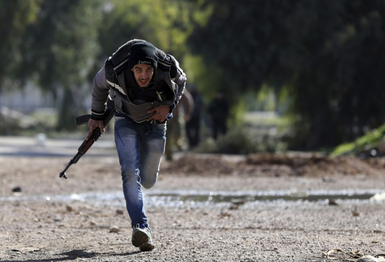 A Free Syrian Army fighter runs for cover at a suburb of Damascus. (Goran Tomasevic/Reuters)