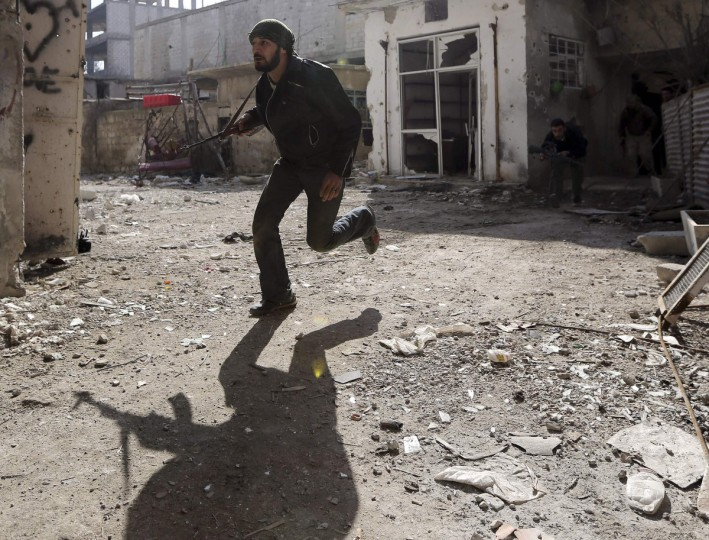 A Free Syrian Army fighter runs for cover in Arabeen neighborhood of Damascus January 19, 2013. (Goran Tomasevic/Reuters)