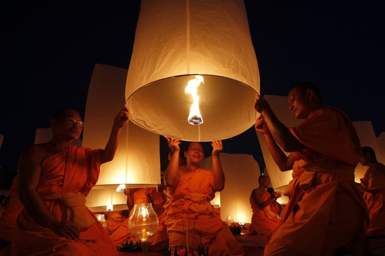 Buddhist monks release paper lanterns into the sky in Suphan Buri province. The lanterns were released during a traditional pilgrimage to pay homage to Lord Buddha and bless Thailand as it enters the new year. (Sukree Sukplang/Reuters)