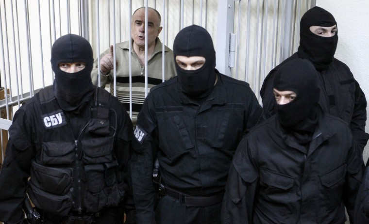 Former Interior Ministry General Alexei Pukach reacts inside a defendant's cage after the verdict was announced during a court session in Kiev. The court announced the verdict to Pukach, who had been charged with murder of opposition journalist Georgiy Gongadze, a well-known reporter who criticized top-level authorities for corruption and fraud, according to local media. Gongadze was kidnapped in central Kiev in 2000 and found dead in a forest outside the capital more than a month later. Pukach was sentenced to life imprisonment, according to local media. (Gleb Garanich/Reuters)