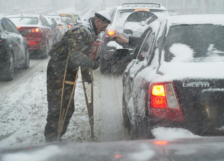 A man, dressed in a military uniform, begs for money at an intersection where cars are stopped, during a snowfall in Kiev. (Gleb Garanich/Reuters)
