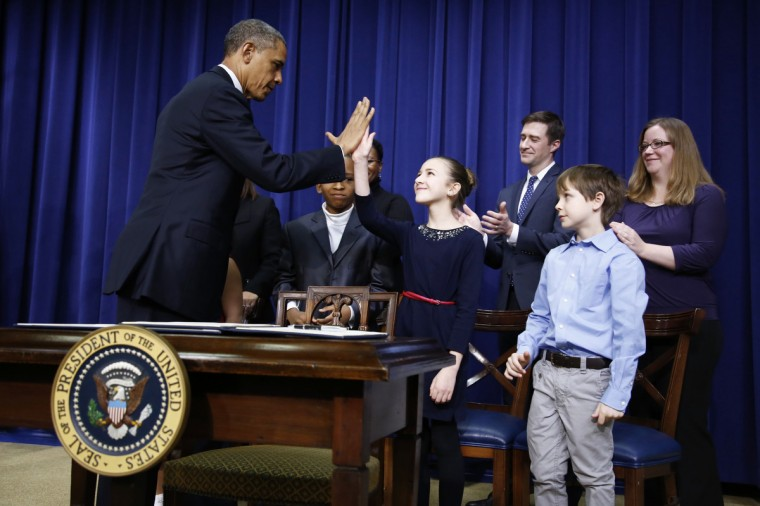 U.S. President Barack Obama (L) high fives children who wrote him letters about guns and gun control before sitting down to sign executive orders on a series of proposals to counter gun violence during an event at the White House in Washington. Vice President Joe Biden delivered his recommendations to Obama after holding a series of meetings with representatives from the weapons and entertainment industries as requested by the president after the December 14 school shooting in Newtown, Connecticut, in which 20 children and six adults were killed. (Jason Reed/Reuters)