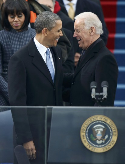 First lady Michelle Obama looks on as U.S. President Barack Obama is greeted by Vice President Joe Biden as he arrives for his swearing-in ceremonies. (REUTERS/Jason Reed)