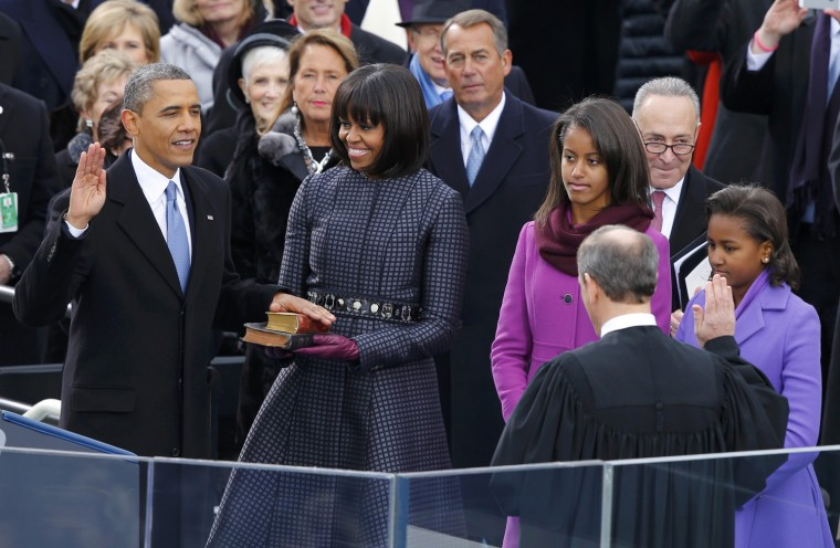 U.S. Supreme Court Chief Justice John Roberts administers the oath of office to U.S. President Barack Obama as first lady Michelle Obama and daughters Malia and Sasha look on. (REUTERS/Jim Bourg)