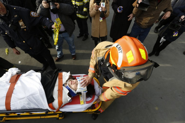 A victim of a commuter ferry crash is cared for by an FDNY EMT on the scene in New York. A commuter ferry crashed into a pier in lower Manhattan early Wednesday, injuring 57 people, one critically, the New York City Police Department said. Passengers lying on stretchers littered the pier near South Street Seaport, attended to by firefighters and rescue workers who rushed to the scene of the 8:43 a.m. (1343 GMT) hard landing. (Brendan McDermid/Reuters)