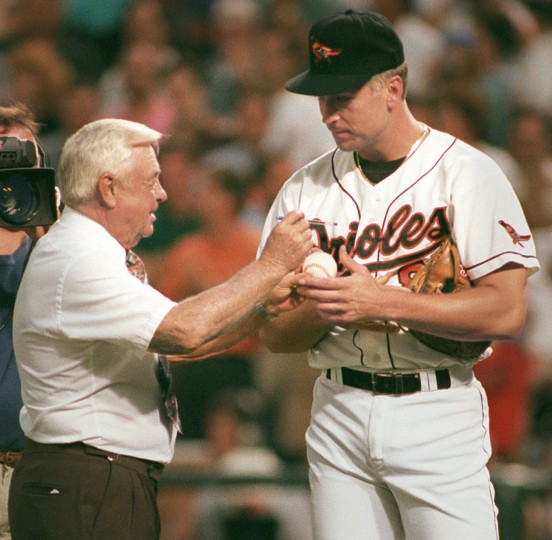 """Sept. 5, 1995: Baltimore Oriole Cal Ripken signs the """"first pitch"""" ball thrown out by Earl Weaver. (Lloyd Fox/Baltimore Sun photo)"""