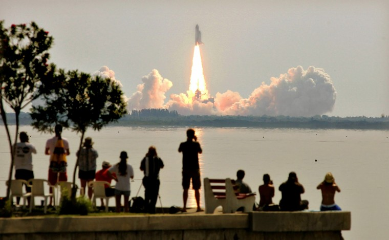 Space Shuttle Discovery lifts off from launch pad 39B at Kennedy Space Center as onlookers watch July 26, 2005 in Titusville, Florida. Discovery is the first shuttle launched since the Columbia disaster over two years ago. (Mario Tama/Getty Images)