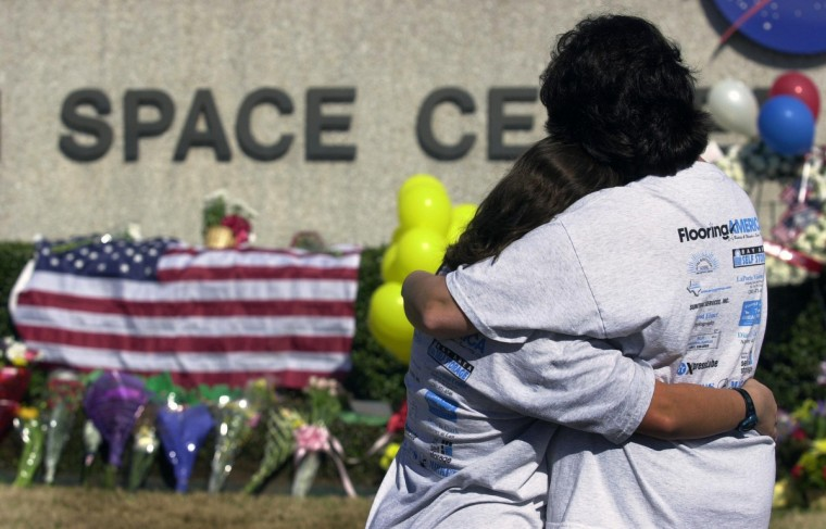 Kathy Kirsh (R) and her daughter Michelle Eggebrecht (L), from Seabrook, Texas console each other outside the Lyndon B. Johnson Space Center in Clear Lake, Texas, 01 February, 2003. Hundreds of people came to the Johnson Space Center to leave flowers in remembrance of the seven astronauts who died 01 February when the US space shuttle Columbia broke apart during re-entry into the earth's atmosphere. Columbia disappeared from radar screens while it was over Texas, 16 minutes before it was due to land at Cape Canaveral in Florida. Several white trails of smoke were seen coming from shuttle as it split up. (Jim Mahoney/Getty Images)