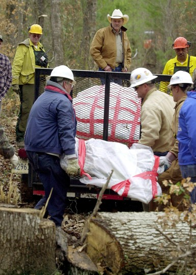 Members of the US Forest Service and the US Environmental Protection Agency loads debris of the nose section of the Space Shuttle Columbia from the woods of Hemphill, Texas, 05 February 2003. The debris will be taken to Barksdale Air Force Base in Louisiana for study. (Eric Gay/Getty Images)