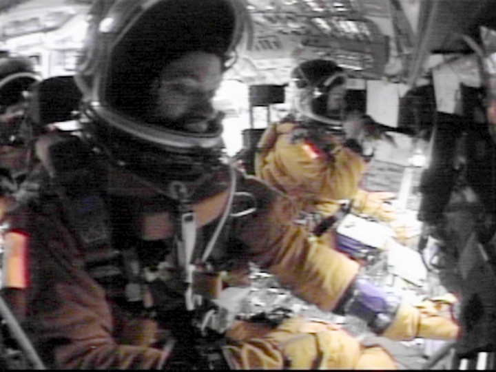 "In this NASA video released 28 February, 2003, space shuttle Columbia pilot William McCool (L) goes through routine entry procedures as commander Rick Husband (R) takes a drink as part of their fluid loading 01 February, 2003 on the flight deck during reentry over the Pacific Ocean for a planned landing in Florida. The video made by the seven astronauts on Columbia shortly before it broke up has been recently found. The partially-damaged tape shows four crew ""doing normal activities"" on the flight deck, some 25 minutes ahead of the scheduled landing, about 10 minutes before the shuttle broke up 01 February over the south-west United States, scattering debris over several states. (NASA video/via Getty)"