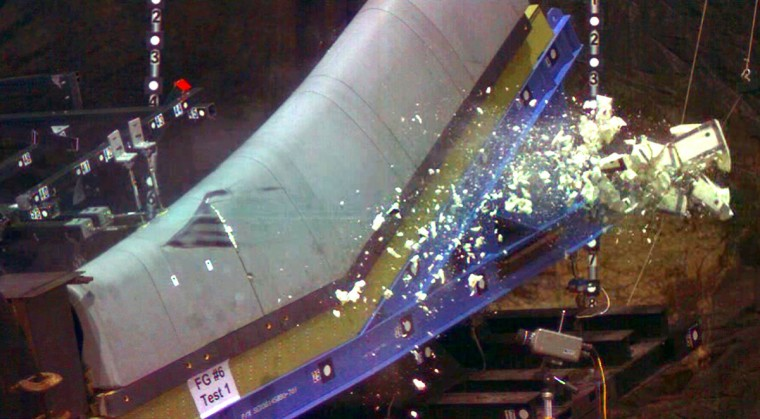 This video image obtained 05 June 2003 courtesy of the Columbia Accident Investigation Board shows a 1.7 pound piece of foam breaking up after being fired at 531mph at a mock-up of a space shuttle wing during tests conducted by the Columbia Investigation Board 29 May. It is suspected that a piece of foam breaking off of the shuttle caused cracks in the wing of Columbia that led to its disintegration on re-entry 01 February 2003. Black mark (L) indicates where foam hit the wing. (Columbia Investigation Board/via Getty)