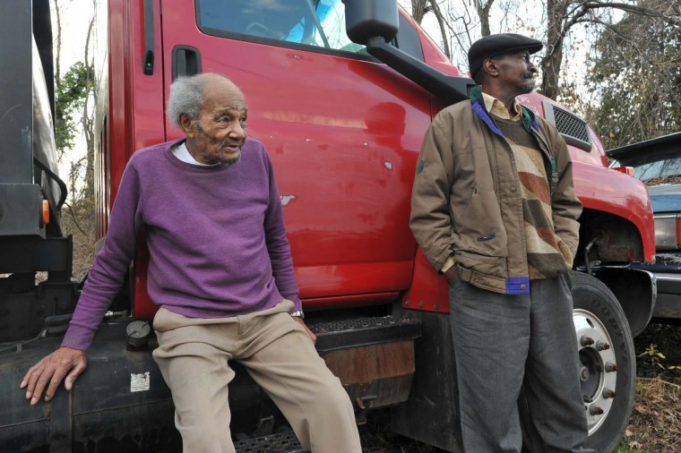 William Walter Scott III, 82, left, visits with his nephew Ricky Scott, in the wooded grove behind the houses that were once filled with their relatives. Scott family members now live in four of the old homes along Falls Road, but at least two of the houses at the north end of the Scott Settlement have been torn down. (Amy Davis/Baltimore Sun)