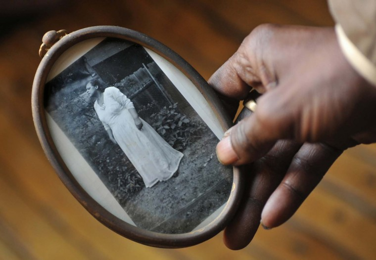 "Ricky Scott holds a 1930's photo of his great-grandmother, Henrietta ""Nanny"" Scott, who helped raise Ricky and his nine siblings. ""She was nice, but strict. There was no talking back to her. If we wanted to play in the quarry on Falls Road we had to do our chores first."" (Amy Davis/Baltimore Sun)"