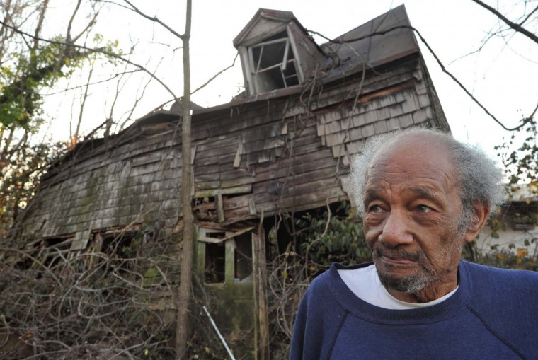 William Walter Scott III, 82, is the patriarch of the remaining Scott clan at Bare Hills. Behind him is the collapsed house built by the founder of the Scott Settlement, the Rev. Aquila Scott, which was destroyed by fire. Rev. Aquila Scott was also a blacksmith and wheelwright on the Falls Road Turnpike. Scott views the changes to the historic family enclave with equanimity. Once primarily a black community, Scott now has a number of white neighbors. (Amy Davis/Baltimore Sun)