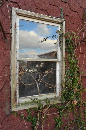 The Bare Hills retail center, with upscale restaurants and stores, is reflected in the window of this empty, deteriorating house in the Scott Settlement. A stone's throw away is a clothing boutique selling $220 blue jeans. (Amy Davis/Baltimore Sun)