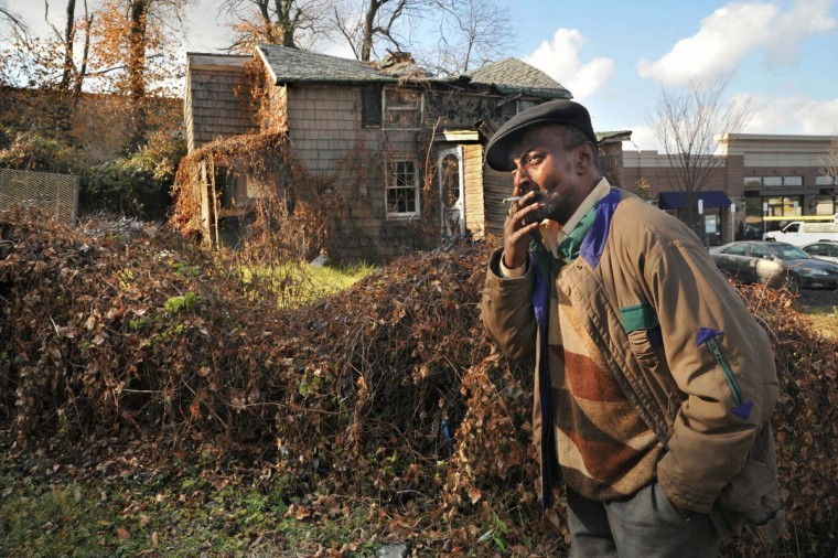 Ricky Scott, 55, who has worked at racetracks and horse farms as a groom, lives in one of the remaining Scott family homes on Falls Road. He spent much of his childhood at the abandoned house behind him, where his grandparents, Catherine and Walter Scott raised his father and two siblings. (Amy Davis/Baltimore Sun)
