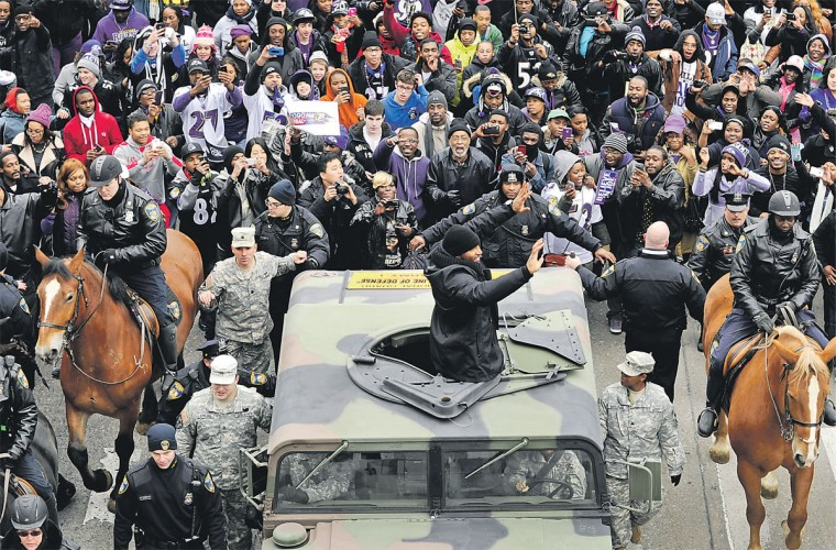 Fans crowd around Ray Lewis and the Ravens during the Super Bowl XLVII victory parade through downtown Baltimore. (Colby Ware/For The Baltimore Sun)