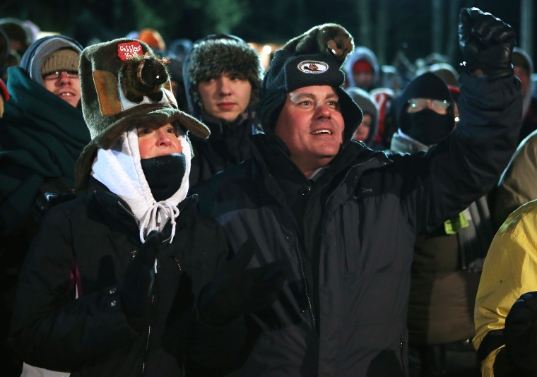 Hank Oxendine (R) of Pottstown, Pennsylvania, waits with his fiance Jennifer Caruso (L) for the Punxsutawney Phil to come out from his winter den during the 127th Groundhog Day Celebration at Gobbler's Knob on February 2, 2013 in Punxsutawney, Pennsylvania. Thousands of people gathered at the event to watch Punxsutawney Phil's annual forecast.  (Photo by Alex Wong/Getty Images)