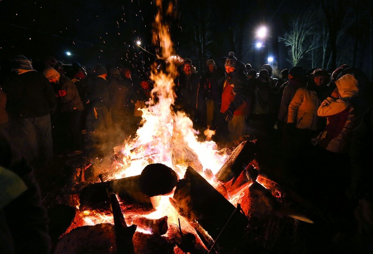 A crowd surround a fire to keep themselves warm during the 127th Groundhog Day Celebration at Gobbler's Knob on February 2, 2013 in Punxsutawney, Pennsylvania. Thousands of people gathered at the event to watch Phil's annual forecast.  (Photo by Alex Wong/Getty Images)