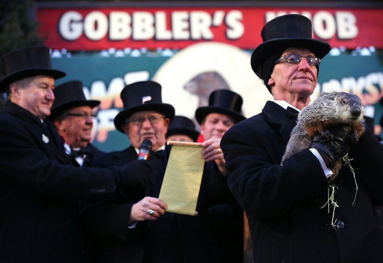 Groundhog co-handler Ron Ploucha (right) holds Punxsutawney Phil as 'His Protector' Bob Roberts (3rd L) reads out the proclamation after Phil didn't see his shadow and predicting an early spring during the 127th Groundhog Day Celebration at Gobbler's Knob on February 2, 2013 in Punxsutawney, Pennsylvania. The Punxsutawney 'Inner Circle' claimed that there were about 35,000 people gathered at the event to watch Phil's annual forecast.  (Photo by Alex Wong/Getty Images)