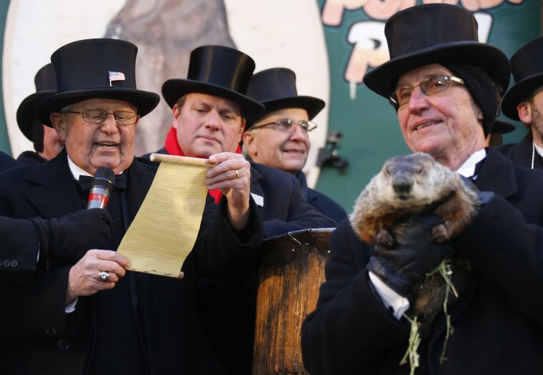 Groundhog co-handler Ron Ploucha (right) holds Punxsutawney Phil as the Groundhog Club's Bob Roberts (L) reads the famous groundhog's annual weather prediction on Gobbler's Knob in Punxsutawney, Pennsylvania, on the 127th Groundhog Day, February 2, 2013. Phil did not see his shadow signaling an early end to winter. REUTERS/Jason Cohn