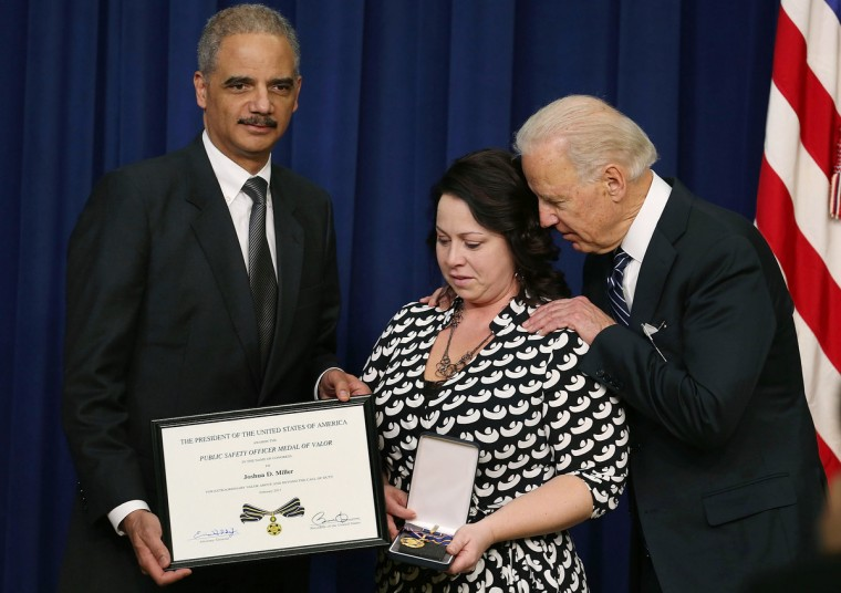 U.S. Vice President Joseph Biden (R) and Attorney General Eric Holder (L) give the Medal of Valor to Angela Miller, widow of fallen Pennsylvania State Trooper Joshua D. Miller, during an event in Eisenhower Executive Office Building in Washington, DC. Vice President Biden presented the award to public safety officers who have exhibited exceptional courage, regardless of personal safety, in the attempt to save or protect others from harm. (Mark Wilson/Getty Images)