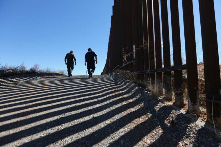 U.S. Customs and Border Protection personnel walk along a section of the recently-constructed fence at the U.S.-Mexico border in Nogales, Arizona. The newest generation of fencing allows Border Patrol agents to see through the fence and is harder to scale from the Mexican side. (John Moore/Getty Images)