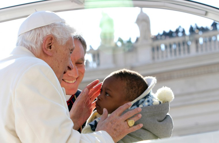 Pope Benedict XVI kisses a child as he arrives in St Peter's Square for his final general audience on February 27, 2013 in Vatican City, Vatican. The Pontiff attended his last weekly public audience before stepping down tomorrow. (Franco Origlia/Getty Images)