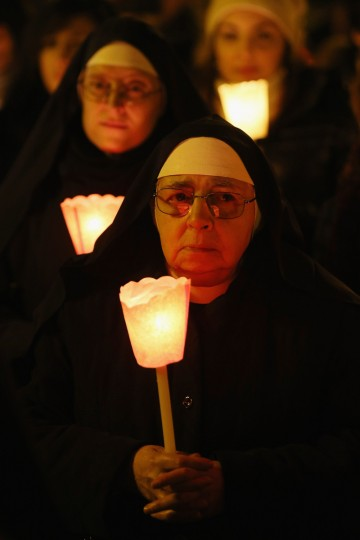 Pilgrims and clergy members hold a candle-lit vigil in Saint Peter's Square, facing Pope Benedict XVI's private apartment, after his final weekly public audience in Vatican City, Vatican. The Pontiff has attended his last weekly public audience before stepping down tomorrow. Pope Benedict XVI has been the leader of the Catholic Church for eight years and is the first Pope to retire since 1415. He cites ailing health as his reason for retirement and will spend the rest of his life in solitude away from public engagements. (Oli Scarff/Getty Images)