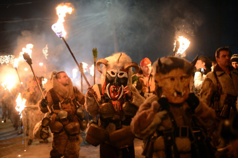 "Bulgarian dancers named ""Kukeri"" hold torches as they perform a ritual dance during the Kukeri Carnival in the village of Batanovci, western Bulgaria, on January 13, 2013. The Kukeri Carnival is a festival of brightly colored masks and costumes which marks the beginning of the spring. Every participant makes his own multi-colored personal mask, covered with beads, ribbons and woolen tassels. The heavy swaying of the main mummer is meant to represent wheat heavy with grain, and the bells tied around the waist are intended to drive away the evil spirits and the sickness. (Dimitar Dilkoff/Getty Images)"