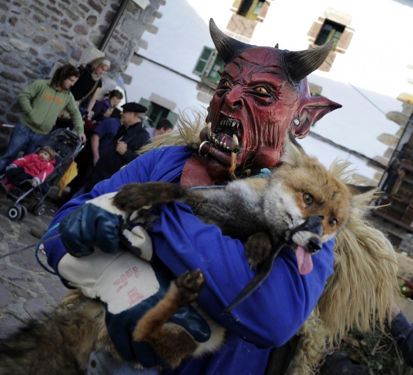 A masked man holds a fox during the carnival of Zubieta, in the northern Spanish province of Navarra province, on January 29, 2013. (Rafa Rivas/Getty Images)