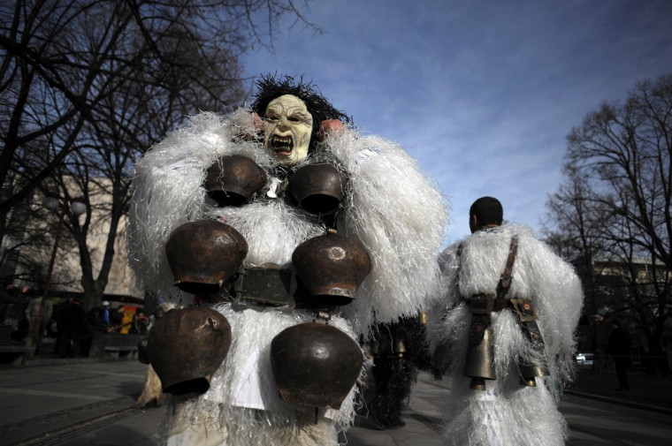 "Bulgarian dancers known as ""Kukeri"" perform a ritual dance during the International Festival of the Masquerade Games in Pernik near the capital Sofia, on February 3, 2013. The three-day festival, which started on February 1, has participants sporting multi-colored masks, covered with beads, ribbons and woolen tassels whlie the main dancer, ladened with bells to drive away sickness and evil spirits, sways like a wheat spikelet heavy with grain. (Nikolay Doychinov/Getty Images)"