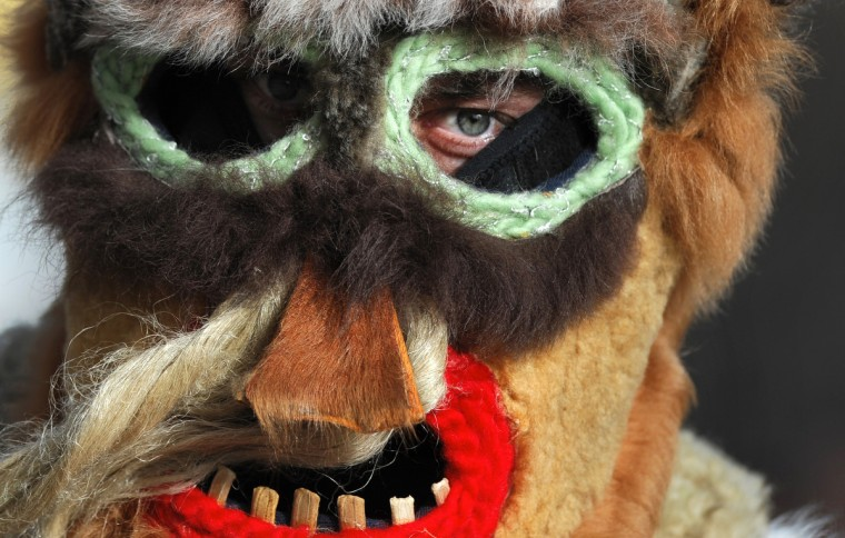 "Bulgarian dancer dressed as ""Kukeri"" performs a ritual dance during the International Festival of the Masquerade Games in Pernik near the capital Sofia, on February 3, 2013. The three-day festival, which started on February 1, has participants sporting multi-colored masks, covered with beads, ribbons and woolen tassels while the main dancer, ladened with bells to drive away sickness and evil spirits, sways like a wheat spikelet heavy with grain. (Nikolay Doychinov/Getty Images)"